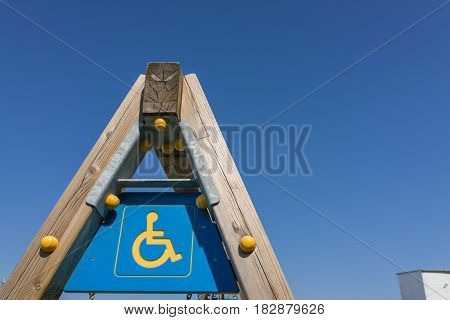 disabled sign and simbol on wooden swing pole playground with clear blue sky. pole playground with clear blue sky.