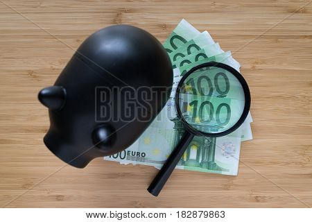Selective focus on magnifying glass on Euro bank note with black piggy bank on wooden table as saving concept