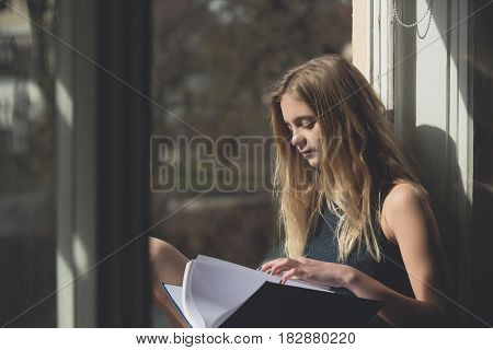 Leisure and relaxing. Pretty girl or young woman student teenager with cute young face and blond long hair in summer dress reading book at open window on urban background