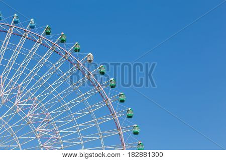 Part of big funfair ferris wheel with clear blue sky background