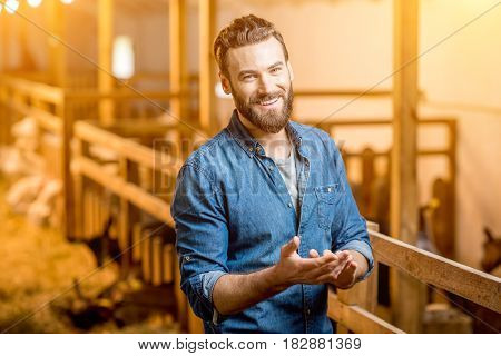 Portrait of a handsome businessman farmer standing in the barn with goats. Natural milk production and farming