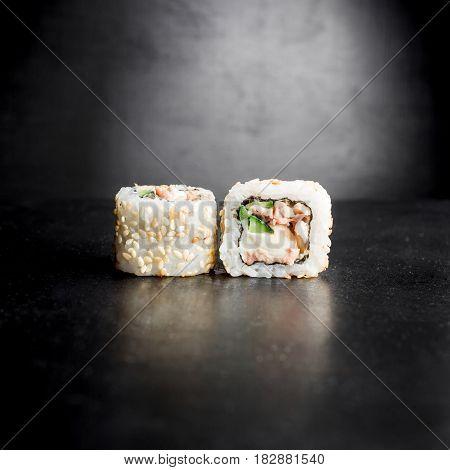 Sushi rolls isolated on dark background. Japanese traditional food.