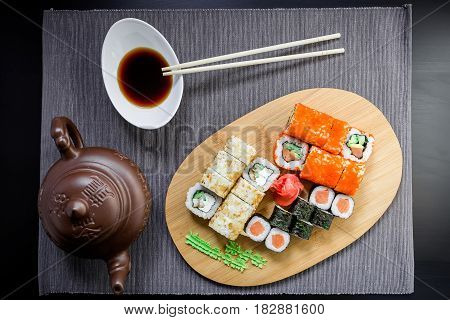 Set sushi rolls, soy sauce, teacup and chopsticks on a grey tablecloth. Top view. Flat lay. Japanese traditional food