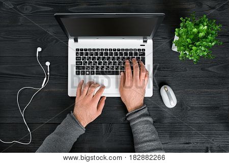 Directly above view of human hands typing on laptop. Laptop, digital tablet and potted plant on work desk. Man working from home.