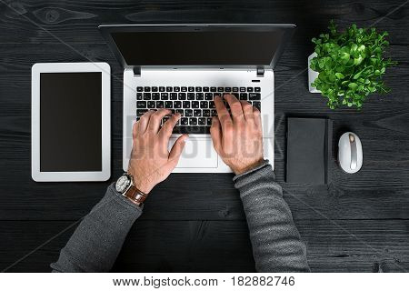 Directly above view of human hands typing on laptop. Laptop, digital tablet, diary and potted plant on work desk. Man working from home.