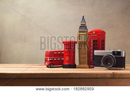 Travel and tourism concept with souvenirs from London and vintage camera on wooden table with copy space