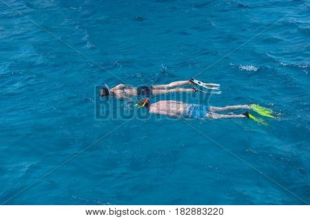 sport hobby. couple of swimmers man and pretty girl or woman with diving masks snorkels flippers snorkeling in transparent sea or ocean water surface on blue background. Idyllic summer vacation.