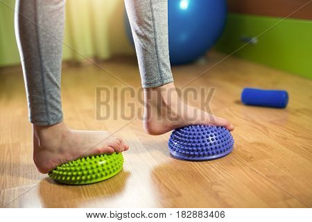 Flat feet correction exercise. Girl walking over spiked half balance massage balls