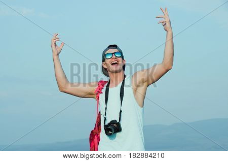 Smiling handsome man photographer with camera or traveler with hands gesture raised to blue sky in stylish fashionable sunglasses and cap on sunny summer day. Photography and hobby