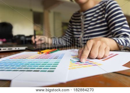 Freelance Graphic Designer Using Digital Tablet, Computer, Woman Working With Color Swatch Catalog S