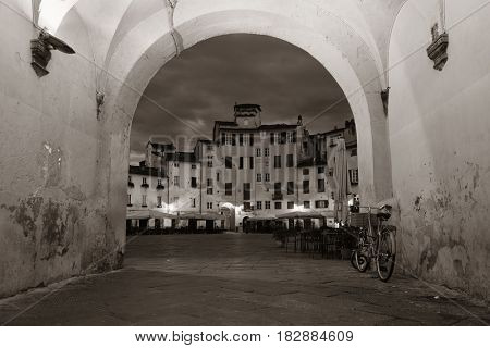 Arch entrance of Piazza dell Anfiteatro in Lucca Italy at night