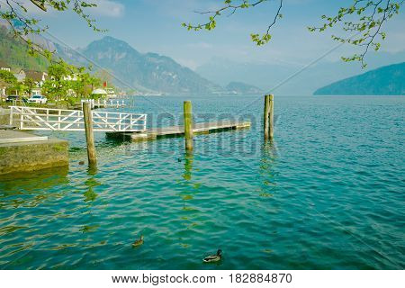 Wooden pier on lake Lucerne Switzerland with mountains