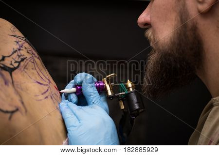 a presentation showing the process of creating a tattoo, hands holding a tattoo machine. The guy with the beard