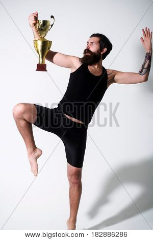 Bearded Man Holds Gold Champion Cup On Grey Background