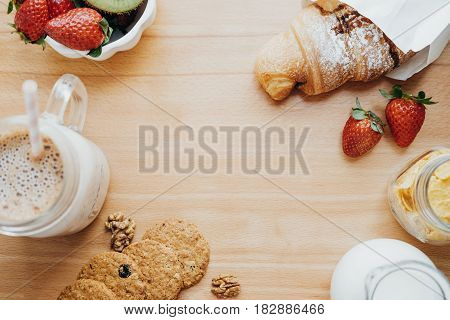 Top View Of Sweet Breakfast With Coffee, Milk, Cookies, Croissant, Strawberry, Kiwi On A Wooden Tabl