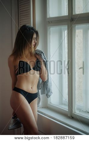 everyday life and household pretty housewife girl with iron shirt has sexy body woman has long hair in erotic lingerie looking out of window family life and housekeeping underwear fashion