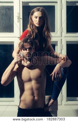 Pretty girl or beautiful woman with long blond hair in red tshirt hugging bearded man hipster or sexy bodybuilder with beard muscular torso abs biceps triceps on misted window