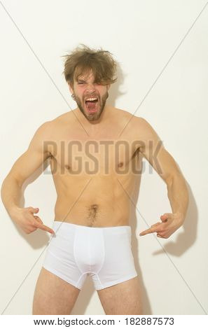Angry man or sexy muscular macho athlete with fit naked torso shouting and finger pointing at white briefs on wall background. Male underwear fashion and fitness