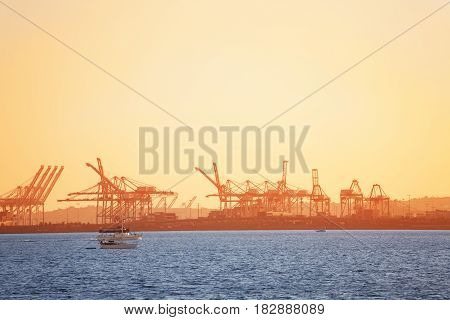 Long Beach shipping port with loading cranes' silhouettes at sunset, California, USA