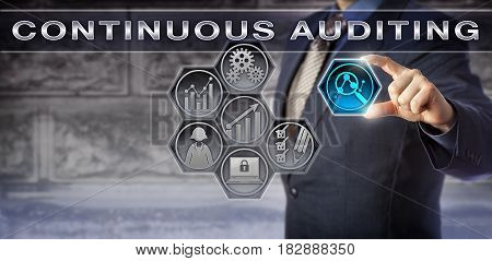Blue chip business executive activating an automated Continuous Auditing process via a virtual touch screen interface. Business concept for internal audit and automatic control and risk assessments.
