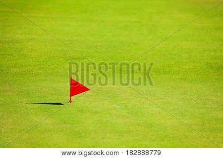 Putting green with red flag marker at end of fairway on the golf course