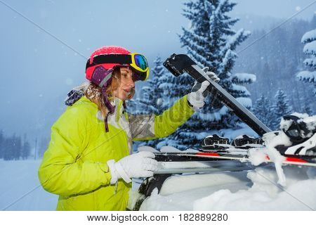 Young woman fastening skis on the roof of car after ski trip to mountains