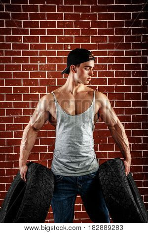 the very muscular handsome sexy guy hold rubber-tire and white, on brick background.