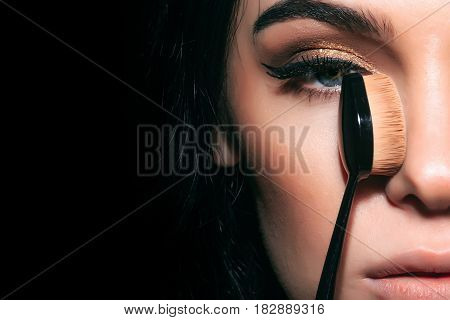 beauty and cosmetics pretty woman or cute sexy girl with brunette hair has long eyelashes and fashionable eye makeup on adorable face holds foundation make up brush near face on black background. spa and skincare visage