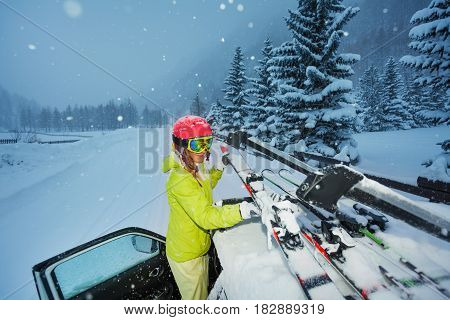 Portrait of young woman fastening skis on the car roof after ski trip in the evening