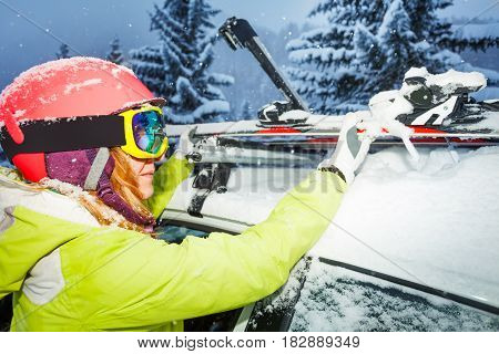 Close-up portrait of female skier fastening skis to roof rails of the car after ski trip to mountains