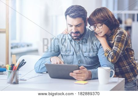 What are you doing, dad. Marked by peace and comfort boy leaning on his father's shoulder and looking at a digital tablet