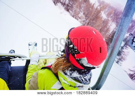 Female skier sitting at chairlift in high mountains, view from her back