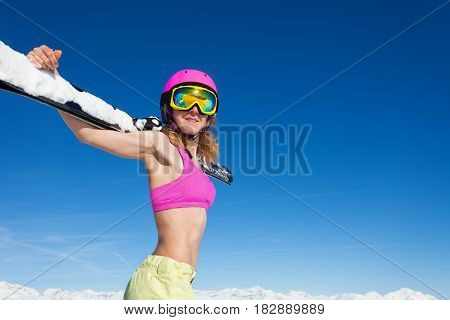 Portrait of cool sporty girl in helmet with ski on her shoulders against winter blue sky