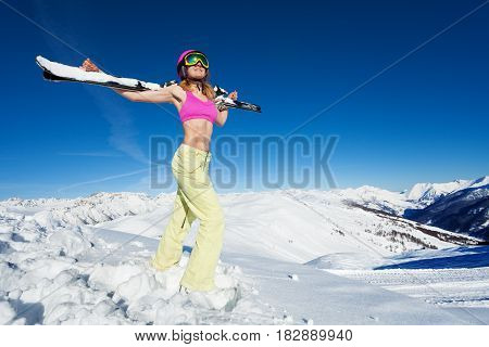 Full-length portrait of active woman in good shape standing with skies on her shoulders and looking upwards