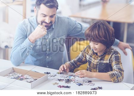 Having a tremendous time. Smiling dad and son building puzzle together while enjoying family time at home