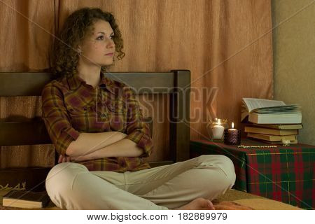 Lonely girl is sitting on bed and thinking