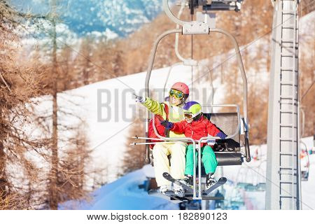Active woman and her son lifting on chairlift,  pointing to snowy peaks with their fingers