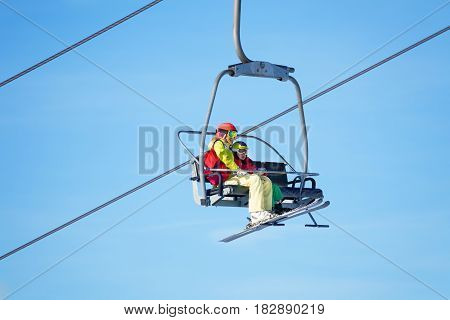 Portrait of mother with her kid son lifting on chairlift  high in the mountains against blue sky