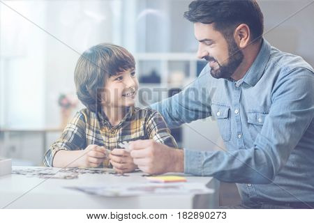 Having fun. Bearded father and smiling son maintaining eye contact while chatting and sorting jigsaw puzzle on a table