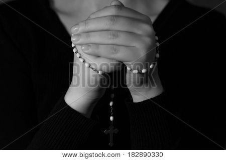 Photo of folded hands with rosary praying person