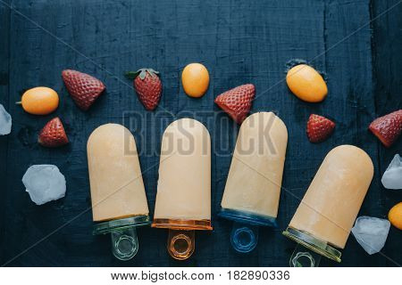 Flat Lay Composition Homemade Fruit Ice Cream With Strawberries And Kumquat On A Black Board.