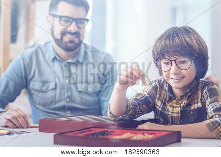 Teaching situation. Amused father wearing glasses teaching son how to play chess and watching little boy getting into the nuts and bolts of the game