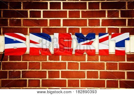 brexit text on Britain national flag backdrop textured by brick wall