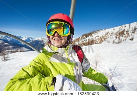 Happy female skier riding up to the top of mountain on chairlift enjoying beautiful view of nature