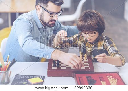 Who is the next chess champion. Happy father and son playing chess at the table while spending time together