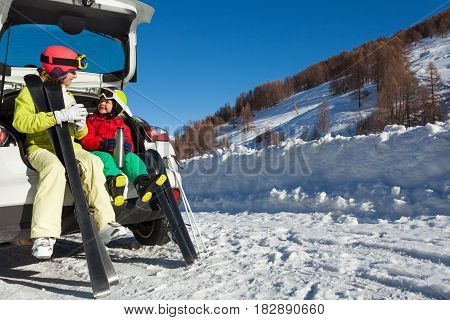 Mother with her son having rest after skiing, sitting in car trunk and drinking warm tea from thermos bottle