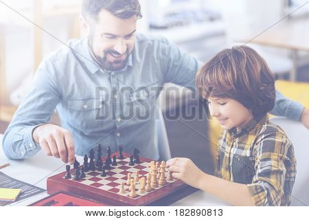 Ready for checkmate. Father and son playing an intense game of chess sitting at a table in a sitting room at home