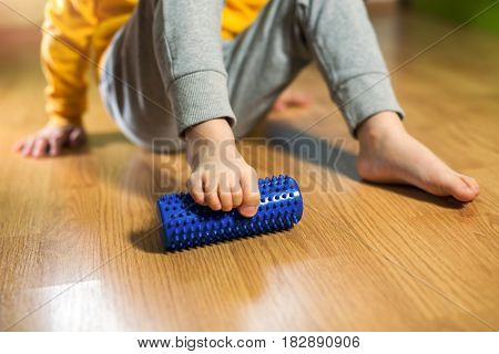 Flat feet correction exercise. Little boy using spiked rubber roller