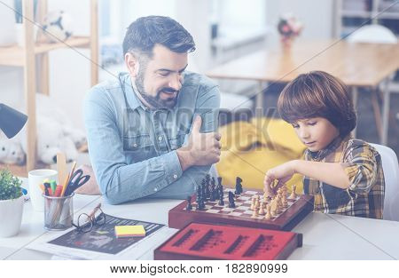 Men's club. Bearded father sitting at a desk with his concentrated little son playing chess at home