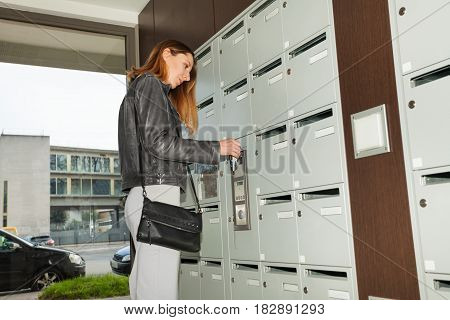 Portrait of young pretty woman closing her mailbox with a key standing at the porch